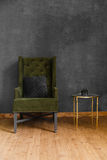 Dark green soft armchair near plaster wall. Arm-chair with fabric upholstery and big vintage mirror in loft style interior stock photo