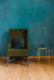 Dark green soft armchair near plaster wall. Arm-chair with fabric upholstery and big vintage mirror in loft style interior stock photos