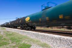 Zipping by dual railroad tracks. Dark green tanker car with yellow markings Royalty Free Stock Image