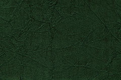 Dark green wavy background from a textile material. Fabric with fold texture closeup. Stock Image