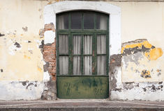 Dark green wooden door in old building facade Stock Photos