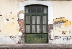 Dark green wooden door in old building facade Stock Photos