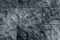 Dark grey background, wall from relief brick. Unusual texture royalty free stock photography