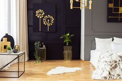 Dark grey bedroom interior with fur rug, gold accessories, simple painting and window with curtains in the real photo stock image