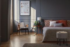 Dark grey bedroom interior. Grey stool in front of bed in dark bedroom interior with armchair against the wall with poster royalty free stock photos