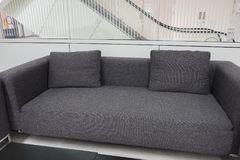 Dark grey fabric sofa in waiting room or contemporary office int Stock Photos