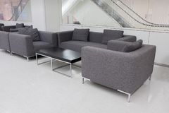 Dark grey fabric sofa in waiting room or contemporary office int Royalty Free Stock Photography