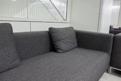 Dark grey fabric sofa in waiting room or contemporary office int Royalty Free Stock Photos