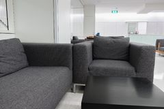 Dark grey fabric sofa in waiting room or contemporary office int Royalty Free Stock Images
