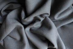 Dark grey fabric in soft folds. Dark grey viscose fabric in soft folds Royalty Free Stock Photos