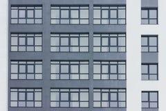 Dark grey facade of building with grey big windows. Big white stripes. Apartment block. Family. Real estate Royalty Free Stock Photos