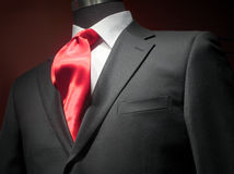 Dark grey jacket with white shirt and red tie. Close-up of a dark grey jacket with white shirt and bright red silk tie Stock Photos