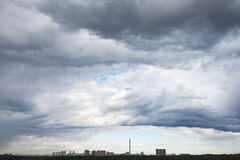 Dark grey rain clouds over city in summer Royalty Free Stock Photography
