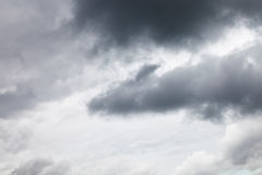 Dark grey rainy clouds in overcast sky stock images
