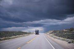Dark grey semi-truck on highway and storming sky Stock Photos