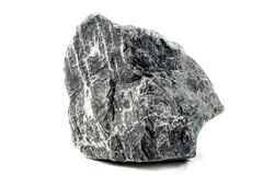Dark Grey Single Nature Stone Of A Different Form Isolated On A White Background. Big Granite Raised Rock. Front View Stock Photo