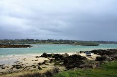 Dark grey sky above the sea with small beach Brittany France Europe royalty free stock image