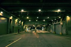 Dark and gritty downtown city street tunnel underpass at night. Royalty Free Stock Photo