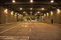 Dark and gritty downtown city street tunnel underpass at night. Stock Image