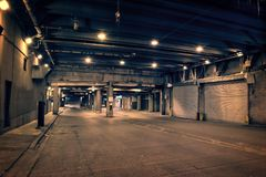 Dark and gritty downtown city street tunnel underpass at night. Royalty Free Stock Photos