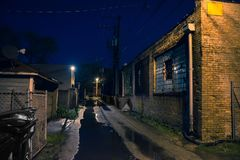 Dark, gritty and wet industrial city alley at night Royalty Free Stock Photography