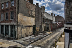 Dark, Grunge, Derelict City Scene. A dark, grunge city scene consisting of a an old cobblestone road and derelict building, with applied filter Stock Photos