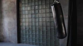 Dark grunge gym, punching bag swinging from the kick, nobody.