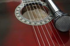 Dark guitar and microphone Stock Photos