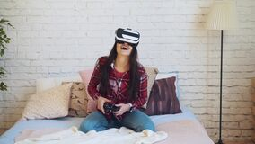 Dark hair caucasian girl controls her gamepad while playing a game in virtual reality glasses before the brick wall. stock video
