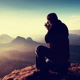 Dark hair man  take photo by  big mirror camera on the neck on the peak of mountains Royalty Free Stock Images