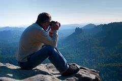 Dark hair man is taking photo by  big mirror camera on the neck on the peak of mountain at sunrise. Royalty Free Stock Photo