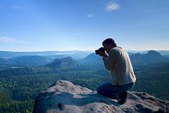 Dark hair man is taking photo by  big mirror camera on the neck on the peak of mountain at sunrise. Royalty Free Stock Image