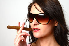 Dark hair woman smoking a cigar with sunglasses Stock Image