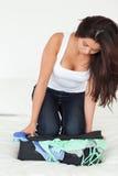 Dark-haired женщина kneeinging на чемодане стоковое фото rf