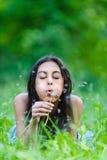 Dark-haired молодая женщина дует прочь стоковое изображение rf