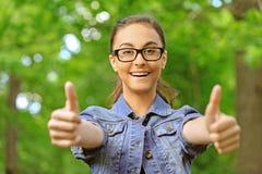 Dark-haired молодая женщина поднимает большой пец руки стоковая фотография