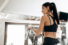 Dark-haired athletic girl dressed in black sports top and tights works out on a treadmill in the gym stock images