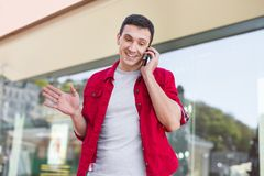 Dark-haired beaming man feeling involved in phone discussion Royalty Free Stock Images