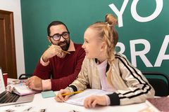 Dark-haired bearded adult teacher in eyewear and his pupil looking amused. Amused. Dark-haired bearded adult teacher wearing eyewear and his pupil looking amused royalty free stock image
