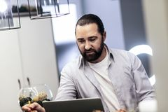 Dark-haired bearded man in a striped shirt looking involved stock photos