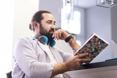Dark-haired bearded man in a striped shirt looking thoughtful royalty free stock image