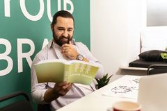 Dark-haired bearded man in a white t-shirt looking amused. Amused. Dark-haired bearded man wearing a white t-shirt looking amused while reading a book on feng stock photography