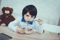 Dark-Haired Boy. Breakfast Alone. Flakes and Milk. Dark-Haired Boy. Breakfast Alone. Flakes with Milk. Spends Time. Happy Together. Leisure Time. Oranges royalty free stock photos