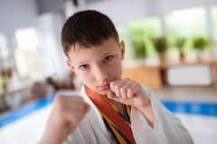 Dark-haired boy wearing kimono for aikido showing fists stock photo
