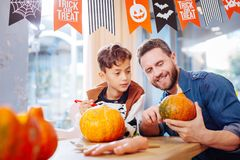 Dark-haired boy wearing skeleton costume watching his father carving pumpkin stock images