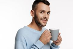 Dark-haired bristled man holding a cup of coffee stock photos