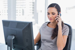Dark haired businesswoman having a phone conversation Stock Image