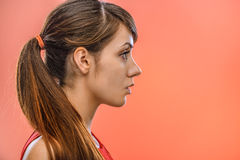 Dark-haired calm woman in profile. Young beautiful dark-haired calm woman in profile, on red background Stock Photo