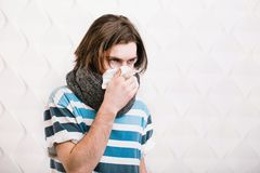 Man Coughs and Blows Nose. Dark-haired caucasian boy coughing and blowing his nose into a tissue, indoor shot of a sick boy in gray scarf and striped t-shirt Royalty Free Stock Photos