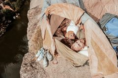 Dark-haired curly woman feeling rested while sleeping in tent with her boyfriend stock images
